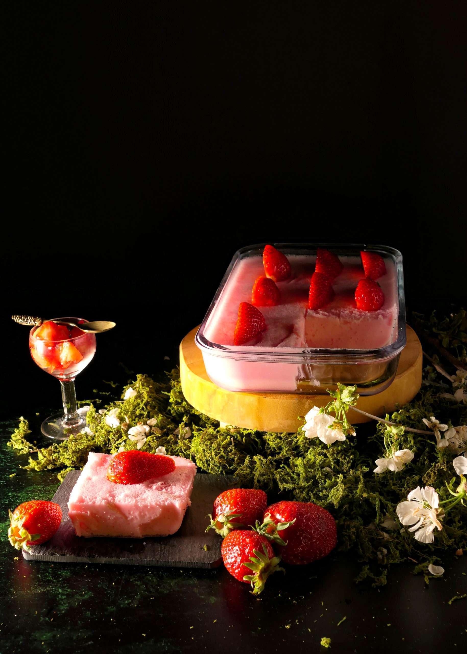un plat avec un gâteau à la gelatine, du yaourt et des fraises